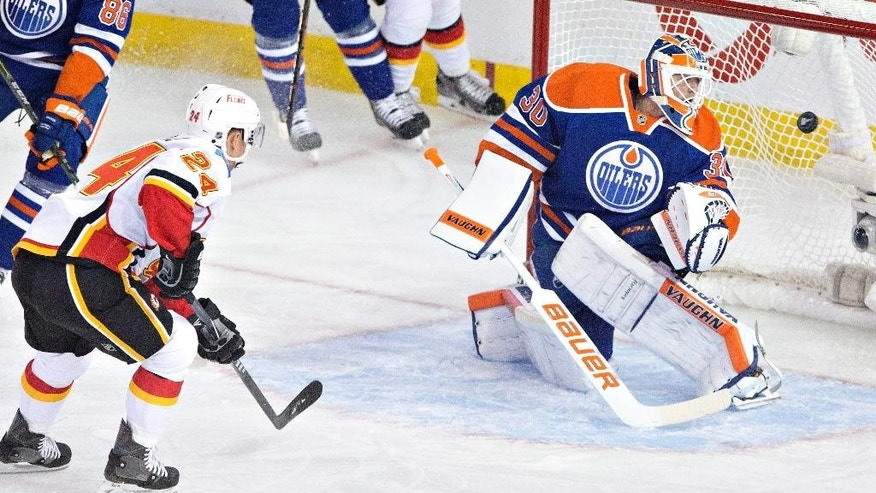 Calgary Flames' Jiri Hudler (24) scores a goal on Edmonton Oilers goalie Ben Scrivens (30) during first period NHL hockey action in Edmonton, Alberta, on Thursday Oct. 9, 2014. (AP Photo/The Canadian Press, Jason Franson)
