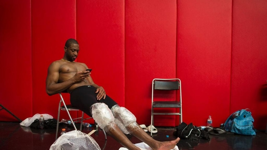 Miami Heat's Dwyane Wade rests with his knees wrapped in ice packs after practice in Rio de Janeiro, Brazil, Friday, Oct. 10, 2014. Miami Heat will play Cleveland Cavaliers in a pre-season game on Saturday as part of the NBA Global Games. (AP Photo/Felipe Dana)