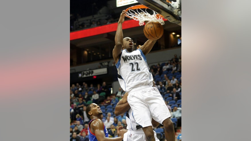 Minnesota Timberwolves rookie Andrew Wiggins dunks in the first quarter of an NBA preseason basketball game against the Philadelphia 76ers, Friday, Oct. 10, 2014, in Minneapolis. Watching, left, is Thaddeus Young. (AP Photo/Jim Mone)