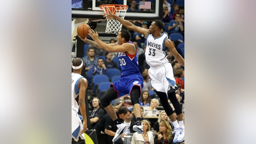 Philadelphia 76ers' Drew Gordon, left, attempts to shoot as Minnesota Timberwolves' Thaddeus Young defends in the first quarter of an NBA preseason basketball game, Friday, Oct. 10, 2014, in Minneapolis. (AP Photo/Jim Mone)