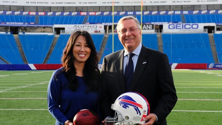 Kim, left, and Terry Pegula are introduced as the new owners of the Buffalo Bills as they pose for members of the media on the football field at Ralph Wilson Stadium in Orchard Park, N.Y., Friday, Oct. 10, 2014. (AP Photo/Gary Wiepert)