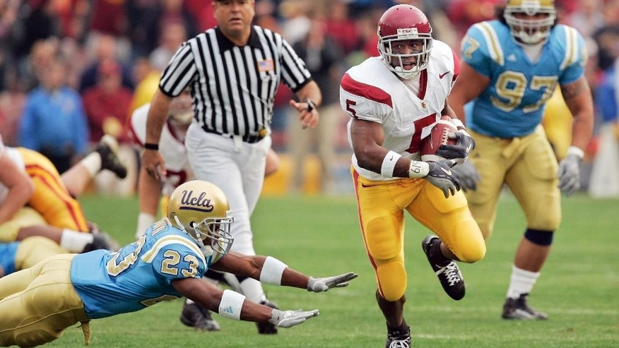 FILE - In this Dec. 4, 2004, file photo, Southern California's Reggie Bush runs for a touchdown as UCLA's Trey Brown, left, misses a tackle while C.J. Niusulu looks on during the first half of an NCAA college football game in Pasadena, Calif. When it comes to powerhouse teams of the BCS-era, Southern California's 2004 edition is the ultimate No. 1. (AP Photo/Mark J. Terrill, File)