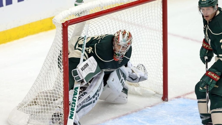 Minnesota Wild goalie Darcy Kuemper peers out of the net as he and Ryan Suter, right, protect it in the third period of an NHL hockey game against the Colorado Avalanche, Thursday, Oct. 9, 2014, in St. Paul, Minn. Kuemper shut out the Avalanche as the Wild won 5-0. (AP Photo/Jim Mone)