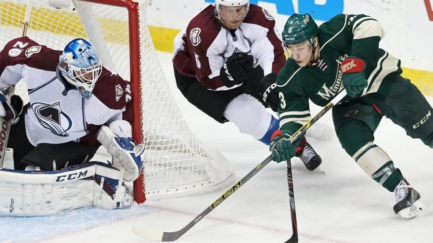 Colorado Avalanche's Erik Johnson, center, defends as Minnesota Wild's Charlie Coyle, right, attempts to shoot on goalie Reto Berra of Switzerland in the third period of an NHL hockey game, Thursday, Oct. 9, 2014, in St. Paul, Minn. The Wild won 5-0. (AP Photo/Jim Mone)