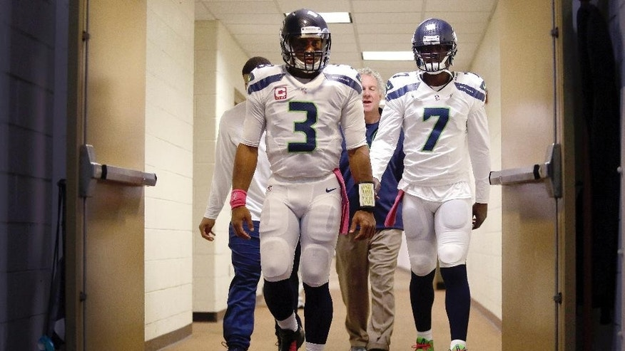 Seattle Seahawks quarterback Russell Wilson (3) and quarterback Tarvaris Jackson (7) walk out of the locker room before an NFL football game against the Washington Redskins in Landover, Md., Monday, Oct. 6, 2014. (AP Photo/Patrick Semansky)