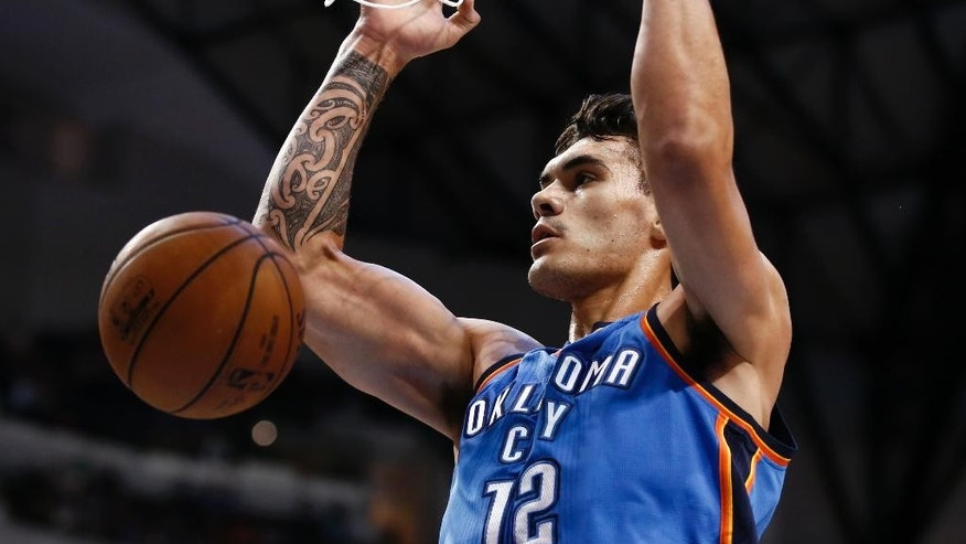 Oklahoma City Thunder center Steven Adams (12) dunks against the Dallas Mavericks during the first half of a preseason NBA basketball game, Friday, Oct. 10, 2014, in Dallas. (AP Photo/Jim Cowsert)