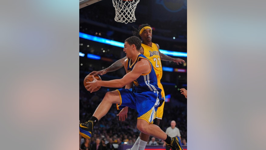 Golden State Warriors guard Klay Thompson, left, passes the ball under pressure from Los Angeles Lakers forward Jordan Hill during the second half of a preseason basketball game, Thursday, Oct. 9, 2014, in Los Angeles.  (AP Photo/Mark J. Terrill)