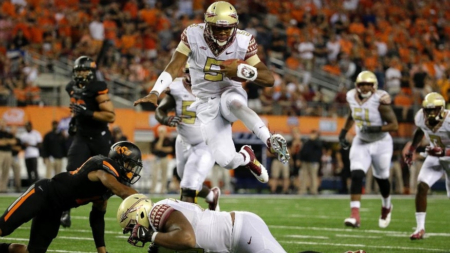 FILE - In this Aug. 30, 2014, file photo, Florida State quarterback Jameis Winston (5) leaps over guard Josue Matias as Oklahoma State safety Jordan Sterns, left, is unable to stop Winston from reaching the end zone for a touchdown in the second half of an NCAA college football game in Arlington, Texas. Winston's quest to become the second player to win two Heisman trophies might already be over. (AP Photo/Tony Gutierrez, File)
