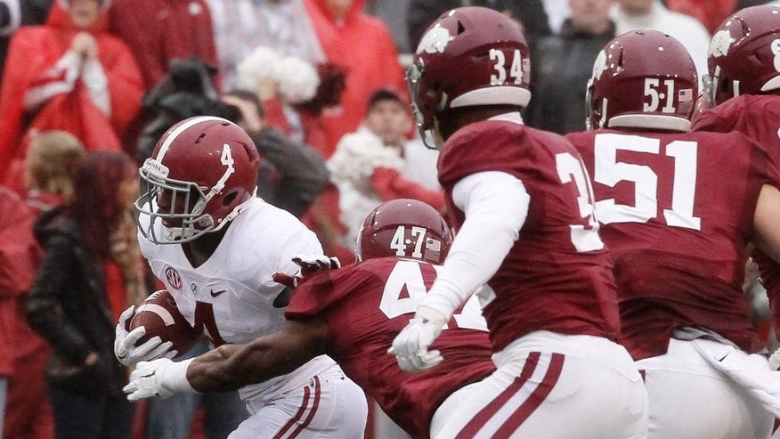 Alabama running back T.J. Yeldon (4) gets past Arkansas defenders linebackers Martrell Spaight (47), Braylon Mitchell (34) and Brooks Ellis (51) in the first half of an NCAA college football game in Fayetteville, Ark., Saturday, Oct. 11, 2014. (AP Photo/Danny Johnston)