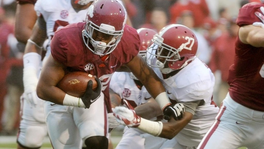 Arkansas running back Jonathan Williams, left, tries to get past Alabama defensive back Nick Perry (27) in the first half of an NCAA college football game in Fayetteville, Ark., Saturday, Oct. 11, 2014. (AP Photo/Sarah Bentham)