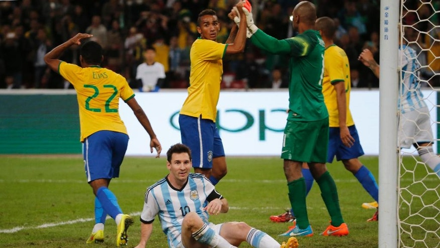Brazil's players react after Argentina's Lionel Messi, center, missed a chance to score  during a Brazil vs. Argentina friendly match at the Bird's Nest National Stadium in Beijing, China, Saturday, Oct. 11, 2014. (AP Photo/Ng Han Guan)