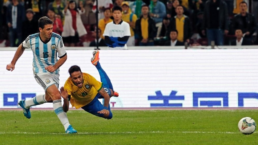 Brazil's Neymar falls as he fights for the ball Argentina's Martin Demichelis during a Brazil vs. Argentina friendly match at the Bird's Nest National Stadium in Beijing, China, Saturday, Oct. 11, 2014. (AP Photo/Ng Han Guan)