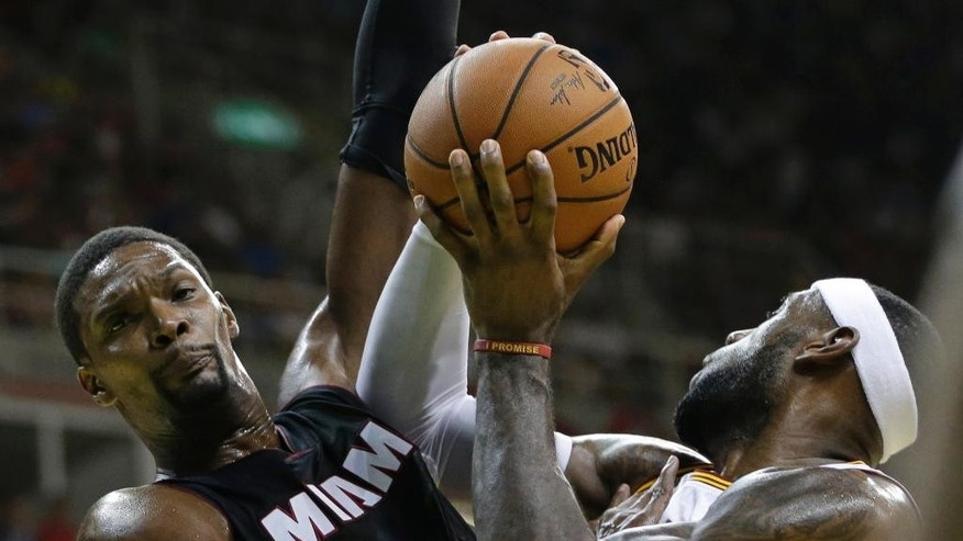 Cleveland Cavaliers' LeBron James, right, tries to shoots past Miami Heat's Chris Bosh during a NBA preseason basketball game that's part of the NBA Global Games, in Rio de Janeiro, Brazil, Saturday, Oct. 11, 2014. (AP Photo/Felipe Dana)