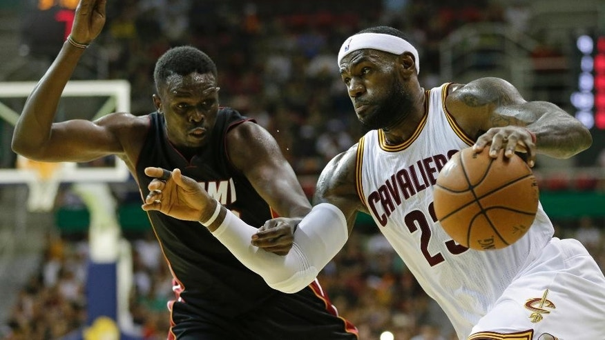 Cleveland Cavaliers' LeBron James, right, drives past Miami Heat's Luol Deng during a NBA preseason basketball game as part of the NBA Global Games, in Rio de Janeiro, Brazil, Saturday, Oct. 11, 2014. (AP Photo/Felipe Dana)