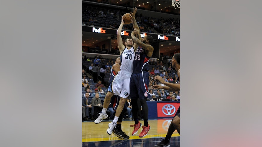 Memphis Grizzlies forward Jon Leuer (30) shoots against Atlanta Hawks forward Mike Scott (32) in the first half of a preseason NBA basketball game, Saturday, Oct. 11, 2014, in Memphis, Tenn. (AP Photo/Brandon Dill)
