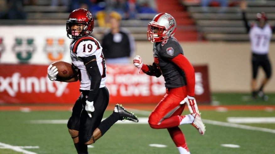 San Diego State's Donnel Pumphrey (19) runs 49-yards for a touchdown against New Mexico's Cranston Jones during the first half of an NCAA college football game Friday, Oct. 10, 2014, in Albuquerque, N.M. (AP Photo/Eric Draper)
