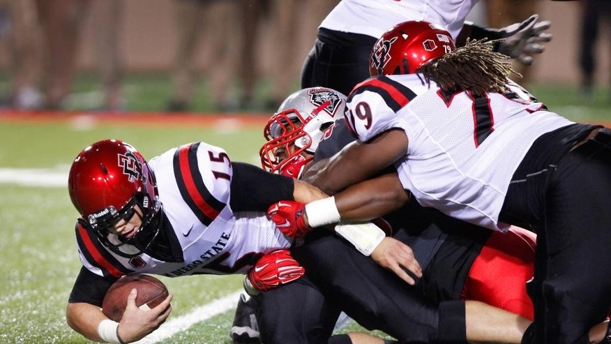 San Diego State quarterback Nick Bawden (15) is sacked by New Mexico players during the first half of an NCAA college football game Friday, Oct. 10, 2014, in Albuquerque, N.M. (AP Photo/Eric Draper)