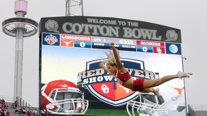An Oklahoma cheerleader flies in the air before an NCAA college football game between Texas  and Oklahoma at the Cotton Bowl, Saturday, Oct. 11, 2014, in Dallas. (AP Photo/LM Otero)