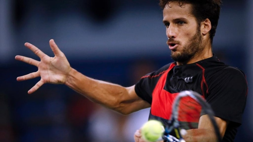 Feliciano Lopez of Spain returns a shot against Gilles Simon of France during their semifinal match at the Shanghai Masters tennis tournament in Shanghai, China, Saturday, Oct. 11, 2014.  (AP Photo/Vincent Thian)