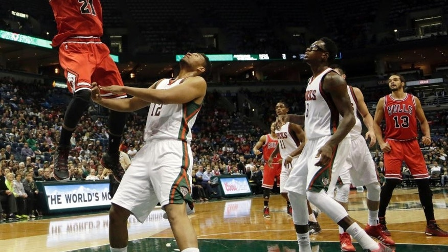 Chicago Bulls guard Jimmy Butler slam dunks against the Milwaukee Bucks during the first half of a preseason NBA game Saturday, Oct. 11, 2014, in Milwaukee. (AP Photo/Darren Hauck)