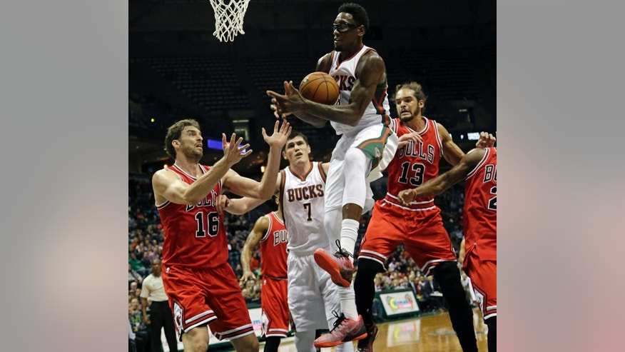 Milwaukee Bucks center Larry Sanders, center, pulls down a rebound against the defense of the Chicago Bulls during the second half of a preseason NBA game Saturday, Oct. 11, 2014, in Milwaukee. (AP Photo/Darren Hauck)