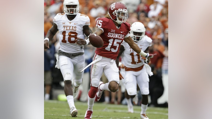 Oklahoma cornerback Zack Sanchez (15) celebrates scoring a touchdown after intercepting a pass against Texas wide receiver Jacorey Warrick (11) and quarterback Tyrone Swoopes (18) during the first half of an NCAA college football game at the Cotton Bowl, Saturday, Oct. 11, 2014, in Dallas. (AP Photo/LM Otero)