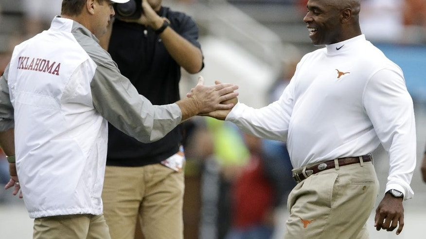 Texas head coach Charlie Strong, right, and Oklahoma head coach Bob Stoops greet each other before an NCAA college football game at the Cotton Bowl, Saturday, Oct. 11, 2014, in Dallas. (AP Photo/LM Otero)