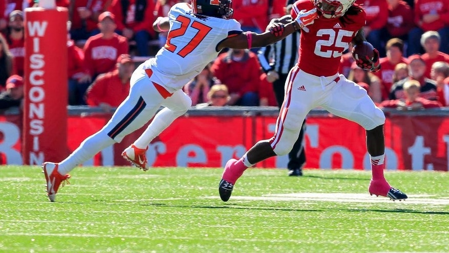 Illinois's Eaton Spence (27) pulls on Wisconsin's Melvin Gordon (25) face mask during the first half of an NCAA college football game Saturday, Oct. 11, 2014, in Madison, Wis. (AP Photo/Andy Manis)