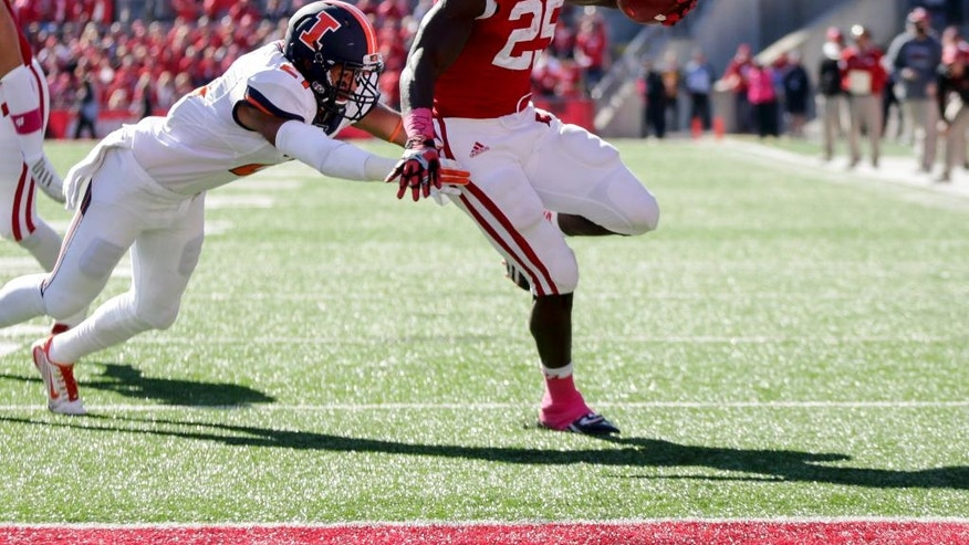 Wisconsin's Melvin Gordon (25) runs past Illinois's Eaton Spence on a touchdown run during the first half of an NCAA college football game Saturday, Oct. 11, 2014, in Madison, Wis. (AP Photo/Andy Manis)