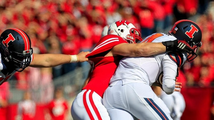 Wisconsin's Ben Ruechel, center, sacks Illinois quarterback Reilly O'Toole during the first half of an NCAA college football game Saturday, Oct. 11, 2014, in Madison, Wis. At left is Illinois' Joe Spencer. (AP Photo/Andy Manis)