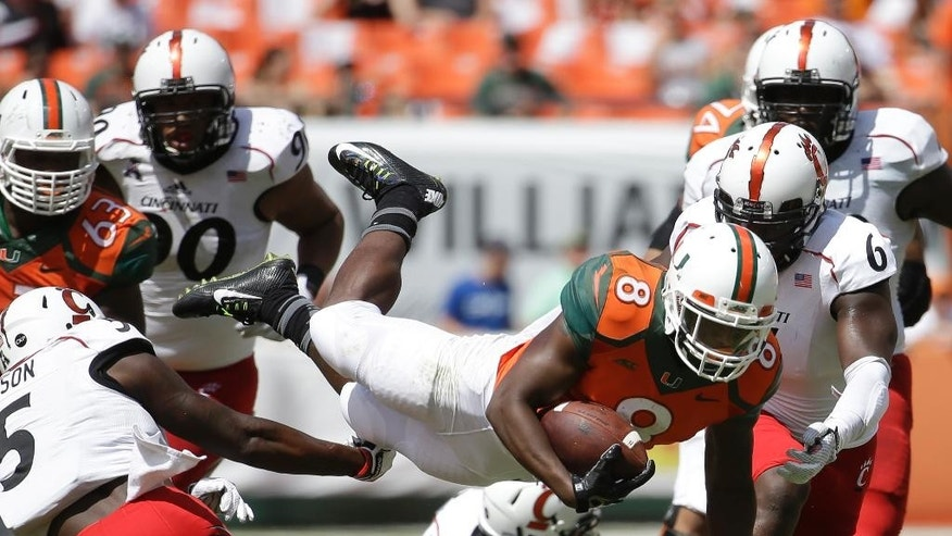 Miami running back Duke Johnson dives ove the line for a first down in the first half of an NCAA college football game against Cincinnati, Saturday, Oct. 11, 2014, in Miami Gardens, Fla. (AP Photo/Lynne Sladky)