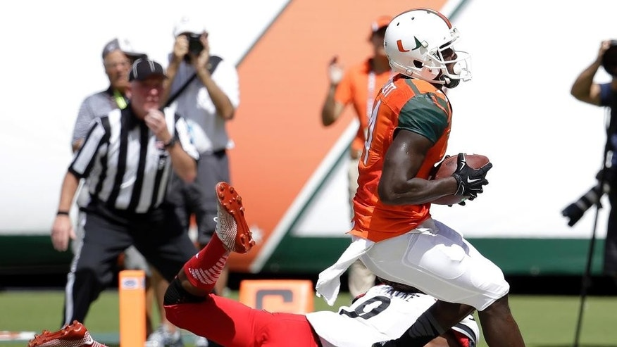 Miami Hurricanes wide receiver Phillip Dorsett scores a touchdown in front of Cincinnati cornerback Leviticus Payne in the first half of an NCAA college football game, Saturday, Oct. 11, 2014, in Miami Gardens, Fla. (AP Photo/Lynne Sladky)