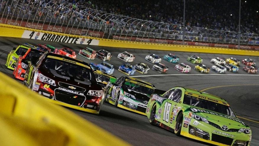 Kyle Busch (18) and Jeff Gordon (24) lead the field at the start of the NASCAR Sprint Cup series Bank of America 500 auto race at Charlotte Motor Speedway in Concord, N.C., Saturday, Oct. 11, 2014. (AP Photo/Chuck Burton)