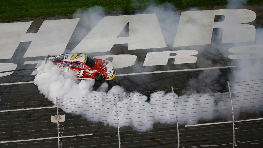 Kevin Harvick (4) burns out after winning the NASCAR Sprint Cup series Bank of America 500 auto race at Charlotte Motor Speedway in Concord, N.C., Saturday, Oct. 11, 2014. (AP Photo/Chris Keane)