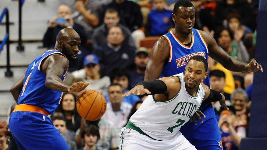 Boston Celtics center Jared Sullinger, center, and New York Knicks forward Quincy Acy, left, reach for a loose ball as New York Knicks center Samuel Dalembert, right, defends during the first during the first quarter of a preseason NBA basketball game , Saturday, Oct. 11, 2014, in Uncasville, Conn. (AP Photo/Jessica Hill)
