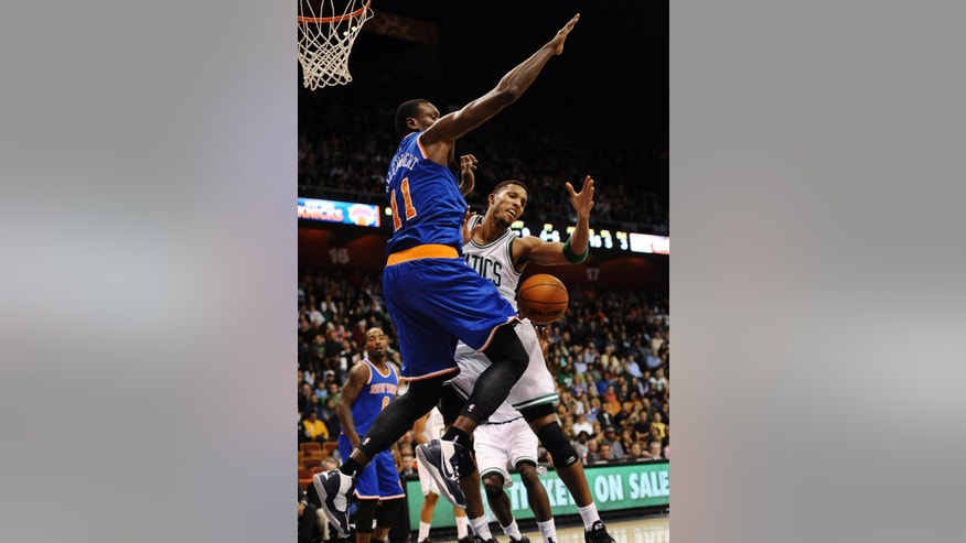 New York Knicks center Samuel Dalembert, left, and Boston Celtics guard Evan Turner, right, collide during the first during the first quarter of a preseason NBA basketball game, Saturday, Oct. 11, 2014, in Uncasville, Conn. (AP Photo/Jessica Hill)
