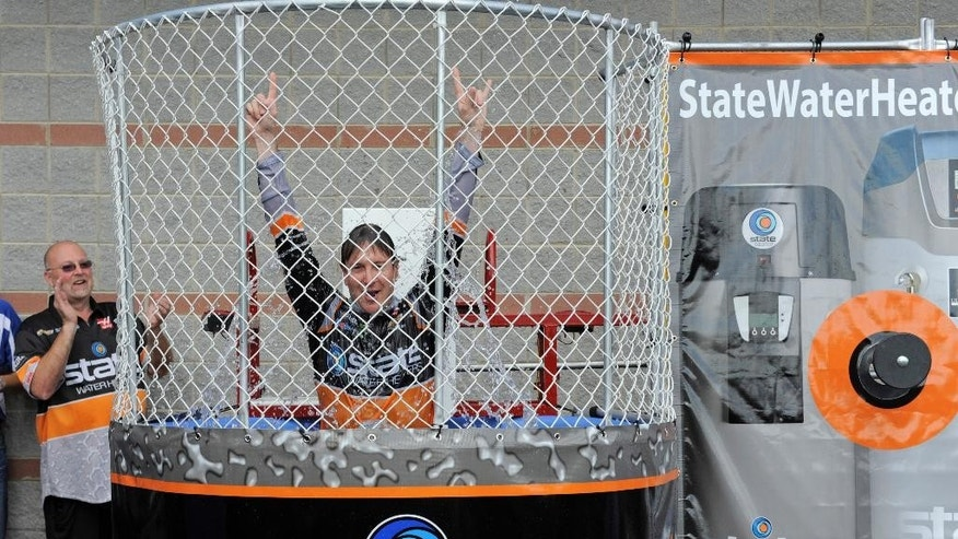 Kurt Busch raises his hands as he is dunked in a dunking booth during a news conference before the NASCAR Sprint Cup series Bank of America 500 auto race at Charlotte Motor Speedway in Concord, N.C., Saturday, Oct. 11, 2014. (AP Photo/Mike McCarn)