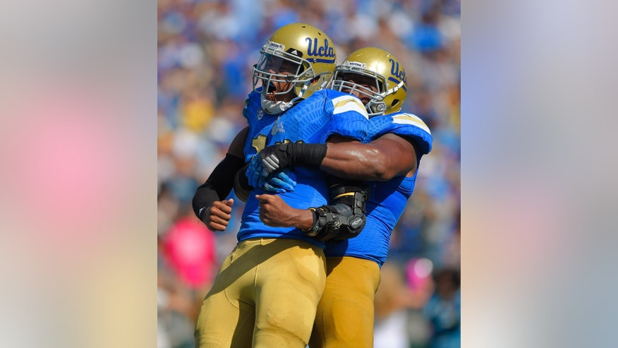 UCLA quarterback Brett Hundley, left, celebrates his touchdown with offensive lineman Malcolm Bunche during the first half of a NCAA college football game against Oregon, Saturday, Oct. 11, 2014, in Pasadena, Calif.  (AP Photo/Mark J. Terrill)