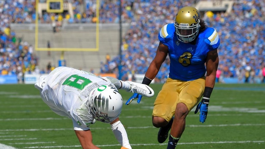 Oregon quarterback Marcus Mariota, left, dives in for a touchdown as UCLA defensive back Adarius Pickett looks on during the first half of a NCAA college football game, Saturday, Oct. 11, 2014, in Pasadena, Calif. (AP Photo/Mark J. Terrill)