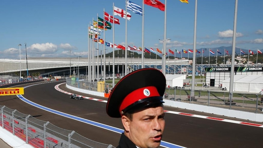 Mercedes driver Lewis Hamilton of Britain steers his car as a local paramilitary member patrols a bridge, during the second free practice at the 'Sochi Autodrom' Formula One circuit , in Sochi, Russia, Friday, Oct. 10, 2014. The inaugural Russian GP will be held on Sunday in Sochi, the Black Sea resort that hosted this year's Winter Olympics. (AP Photo/Luca Bruno) (AP Photo/Luca Bruno)