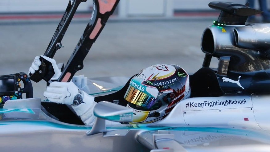 Mercedes driver Lewis Hamilton of Britain, removes a part of his car after setting the qualifying session at the 'Sochi Autodrom' Formula One circuit , in Sochi, Russia, Saturday, Oct. 11, 2014. The inaugural Russian GP will be held on Sunday in Sochi, the Black Sea resort that hosted this year's Winter Olympics. (AP Photo/Luca Bruno)