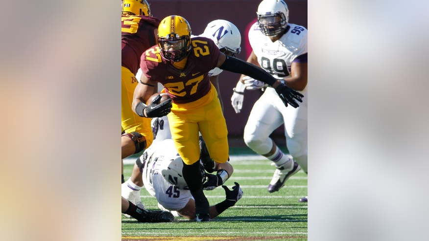 Minnesota running back David Cobb (27) evades Northwestern linebacker Collin Ellis (45) during the first quarter of an NCAA college football game in Minneapolis Saturday, Oct. 11, 2014. (AP Photo/Ann Heisenfelt)