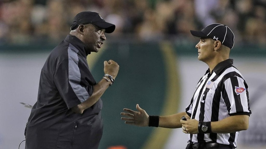 East Carolina head coach Ruffin McNeill, left, gestures at line judge Baron Ballester after his team was called for a penalty against South Florida  during the second quarter of an NCAA college football game, Saturday, Oct. 11, 2014, in Tampa, Fla. (AP Photo/Chris O'Meara)