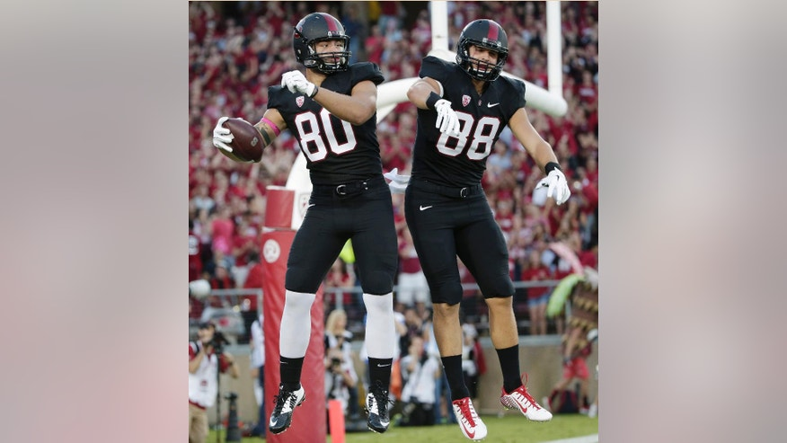Stanford tight end Eric Cotton, left, celebrates his touchdown reception with teammate Greg Taboada during the first half of an NCAA college football game on Friday, Oct. 10, 2014, in Stanford, Calif. (AP Photo/Marcio Jose Sanchez)