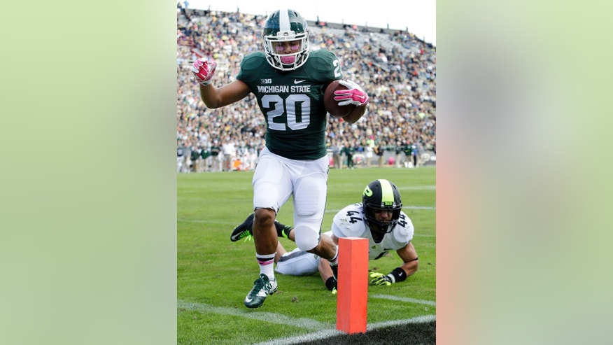 Michigan State running back Nick Hill (20) scores a touchdown in front of Purdue safety Landon Feichter (44) during the first quarter of an NCAA college football game in West Lafayette, Ind., Saturday, Oct. 11, 2014. (AP Photo/AJ Mast)