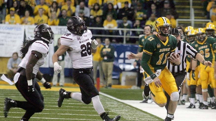 North Dakota State quarterback Carson Wentz (11) turns the corner on a scramble against Southern Illinois defenders in the first half of an NCAA college football game Saturday, Oct. 11, 2014, in Fargo, N.D. (AP Photo/Bruce Crummy)