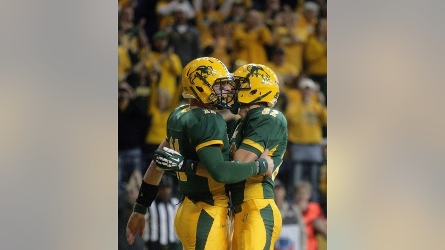 North Dakota State quarterback Carson Wentz, left, celebrates his touchdown run with wide receiver Zach Vraa (82) during the first half of an NCAA college football game against Southern Illinois, Saturday, Oct.  11, 2014, in Fargo, N.D. (AP Photo/Bruce Crummy)