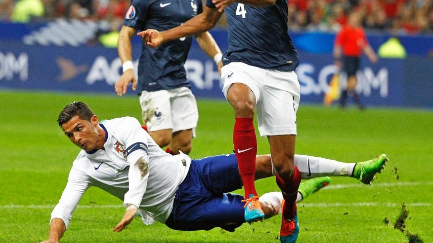 Portugal player Cristiano Ronaldo, center, fights for the ball with French player Rafael Varane, during the international friendly soccer match between France and Portugal at the Stade de France in Saint Denis, north of Paris, Saturday, Oct. 11, 2014. (AP Photo/Remy de la Mauviniere)
