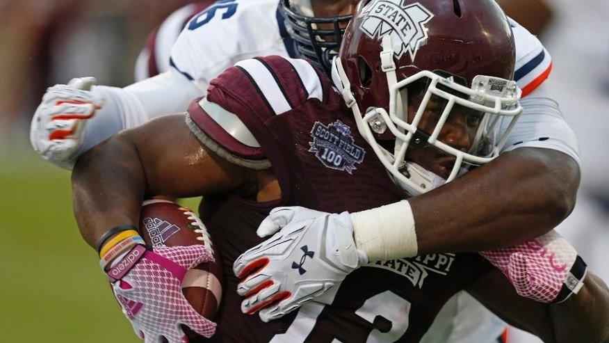 Mississippi State running back Josh Robinson (13) is tackled by Auburn defensive lineman DaVonte Lambert (86) after a run during the first half of an NCAA college football game in Starkville, Miss., Saturday, Oct 11, 2014.  (AP Photo/Rogelio V. Solis)