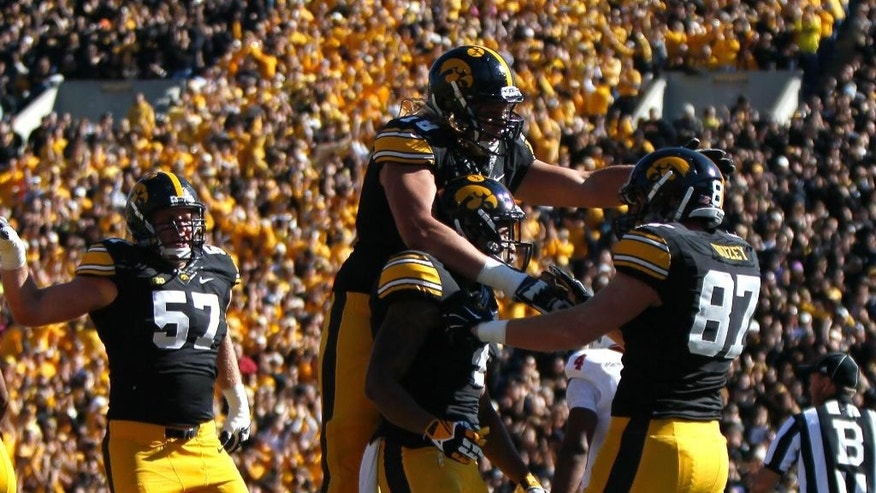 Iowa's tight end Jake Duzey, right, celebrates his touchdown with offensive lineman Andrew Donnal, top, and wide receiver Tevaun Smith, bottom, during the first half of an NCAA college football game against Indiana Saturday, Oct. 11, 2014, in Iowa City, Iowa. (AP Photo/Matthew Putney)